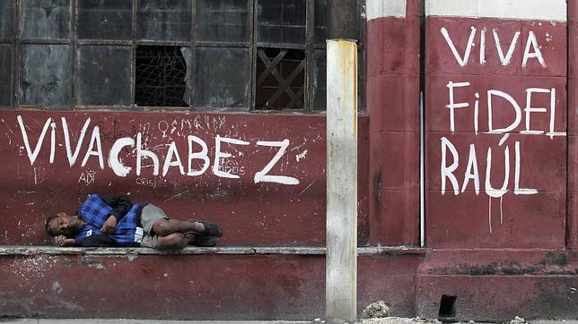 Un cubano descansa junto a un grafiti partidario del castrismo y del chavismo en una calle de La Habana