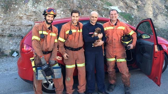 Imagen de los bomberos con el cachorro rescatado
