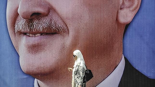 Una mujer pasa junto a un enorme retrato de Erdogan en Estambul