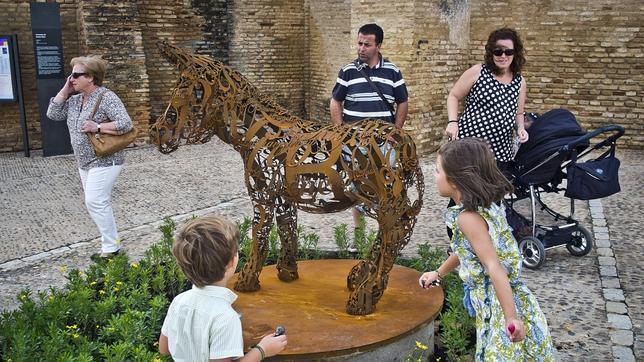 """Platero y yo, homenajeado: una familia observa la nueva escultura del museo al aire libre """"Platero Es-cultura"""", ubicada en la plaza de Las Monjas de Moguer (Huelva)"""