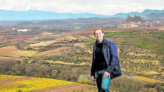 En otoño, el color de las vides delata su variedad, explica Santiago Vivanco, que posa con el Castillo de Davadillo al fondo