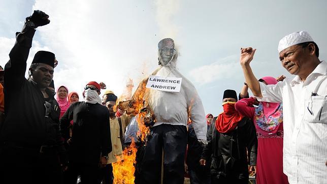 Musulmanes queman un muñeco con el retrato del sacerdote católico Lawrence Andrew, editor del semanario «Herald»