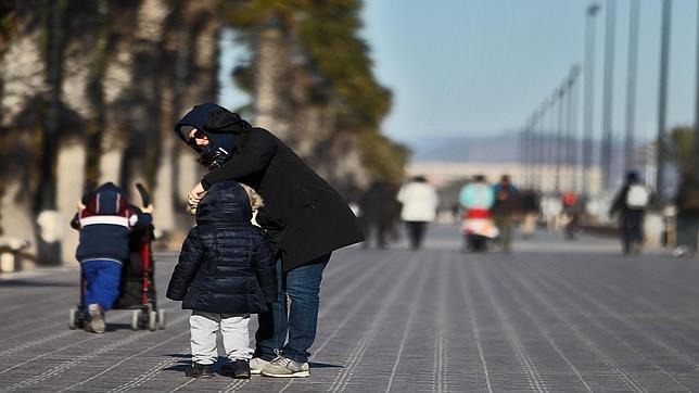 Una mujer protege a un niño del frío en el paseo marítimo de Valencia