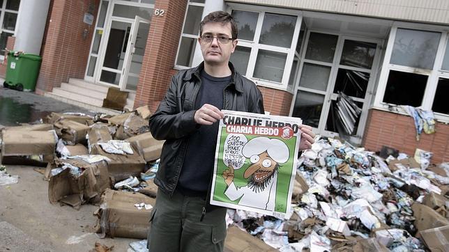Charb, el director de Charlie Hebdo, con un ejemplar del semanario tras un ataque a sus oficinas en 2011