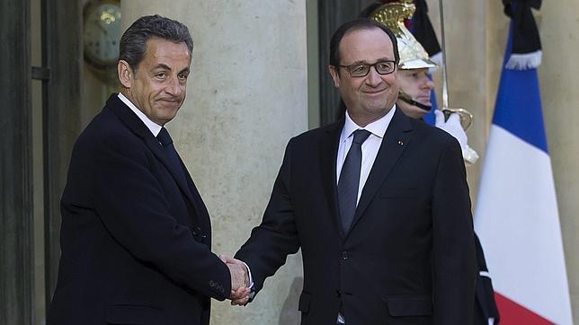 El presidente galo, François Hollande (dcha), estrecha la mano al expresidente francés y líder opositor Nicolas Sarkozy (izq), tras mantener una reunión en el Palacio del Elíseo en París (Francia)