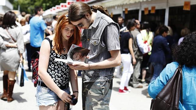 Dos jóvenes, leyendo un libro en la última Feria del Libro de Madrid