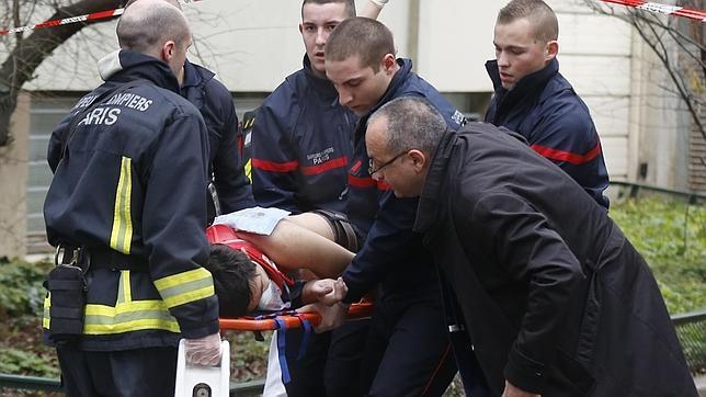 Traslado de uno de los heridos en el tiroteo en la sede de la revista satírica francesa