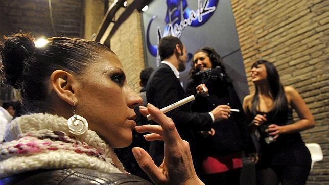 Una joven fuma un cigarrillo