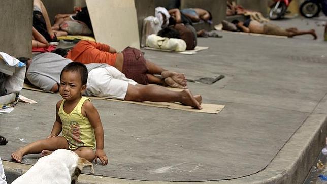 Unos niños vagabundos juegan en una calle de Manila (Filipinas)