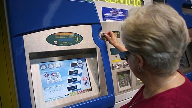 Una mujer introduce el importe del billete sencillo en una máquina expendedora