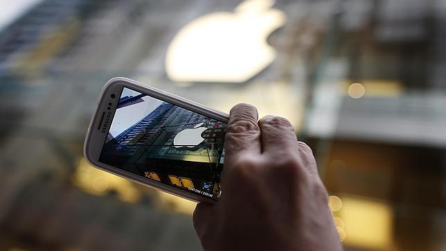 Un usuario de un teléfono de Samsung toma una fotografía del logo de Apple