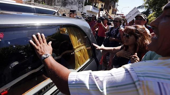 Argentinos tocan el coche fúnebre con los restos del fiscal Alberto Nisman a las puertas del cementerio de La Tablada