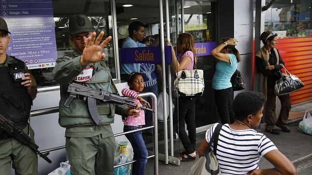 La Guardia Nacional venezolana vigila la entrada de un supermercado de Caracas