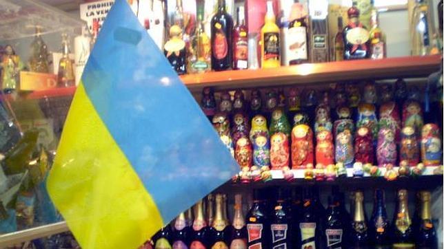 La bandera de Ucrania sobre un fondo formado de muñecas rusas, en una tienda de comida de Europa del este.