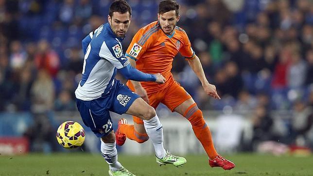 El defensa del Español Arbilla (i) disputa un balón a Piatti, delantero del Valencia