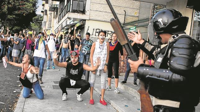 Miembros de la Policía Nacional Bolivariana se enfrentan a manifestantes en Caracas