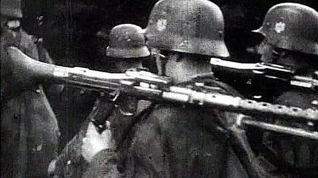 Diferentes soldados precedidos de un combatiente armado con una ametralladora pesada