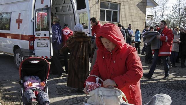 Varias personas hacen cola durante el reparto de material por parte de la Cruz Roja
