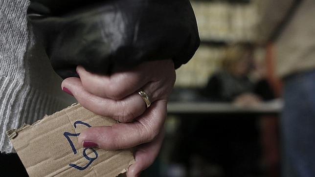 Una mujer espera para recibir una bolsa con comida en un banco de alimentos de Atenas