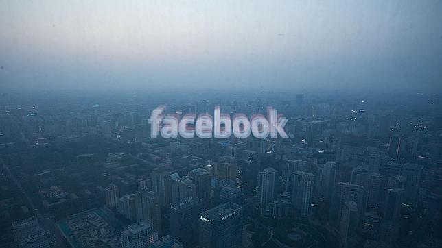 El logotipo de Facebook se refleja en una ventanal con la panorámica de Pekín