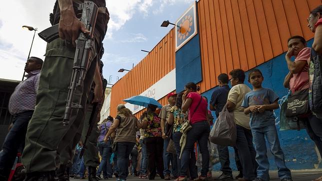 Venezolanos hacen cola junto a un supermercado Día a Día, en Caracas