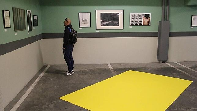 Un espectador contempla algunas de las obras expuestas en Lacolect