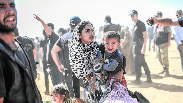 Una de las imágenes del año de AFP, en la que se puede ver a una mujer kurda con sus hijos, atravesando la frontera turco-siria