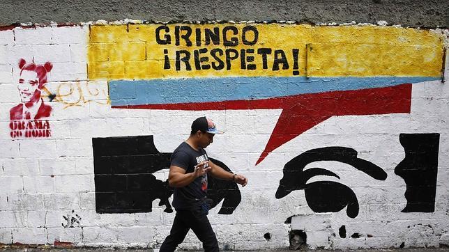 Un transeúnte pasa junto a un grafiti crítico con EE.UU. en una calle de Caracas