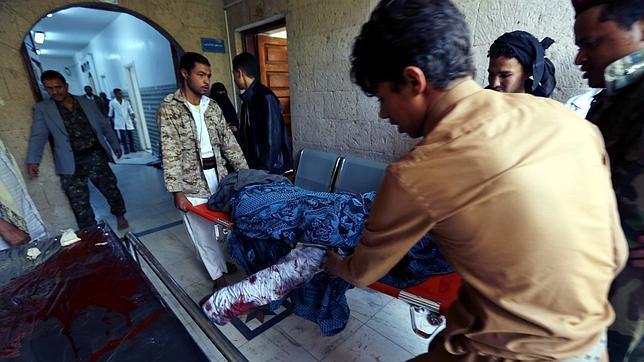 Yemeníes trasladan el cuerpo de una mujer muerta tras los ataques con explosivos contra dos mezquitas chiíes