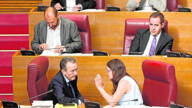 Mónica Oltra dialoga con el portavoz y parlamentario del PSPV, Antonio Torres, en los escaños del grupo socialista