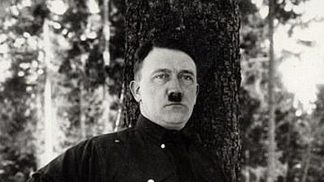 En la instantánea se muestra al líder nazi apoyado sobre un árbol con pantalones cortos y calcetines hasta la rodilla