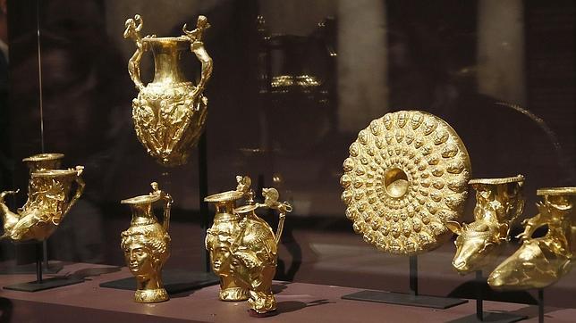 Una mujer observa piezas de oro tracias expuestas en el Louvre