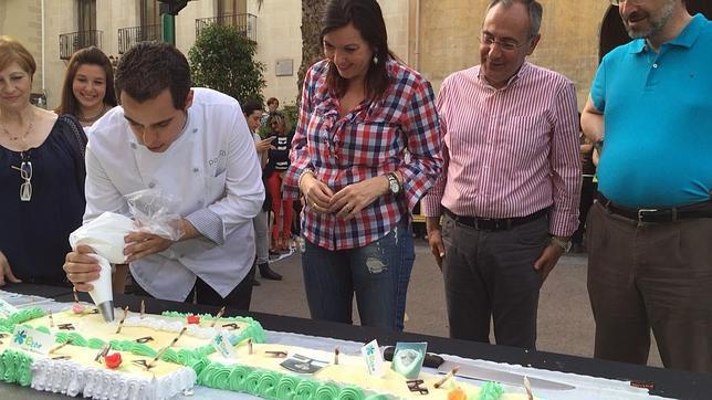 Daniel Patiño trabaja en la elaboración de la tarta ante la mirada de la alcaldesa de Elche
