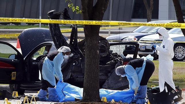 Varios operarios trabajan en el lugar donde dos hombres fueron tiroteados en Texas
