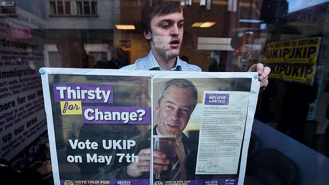 Un hombre cuelga un cartel de apoyo a Farage