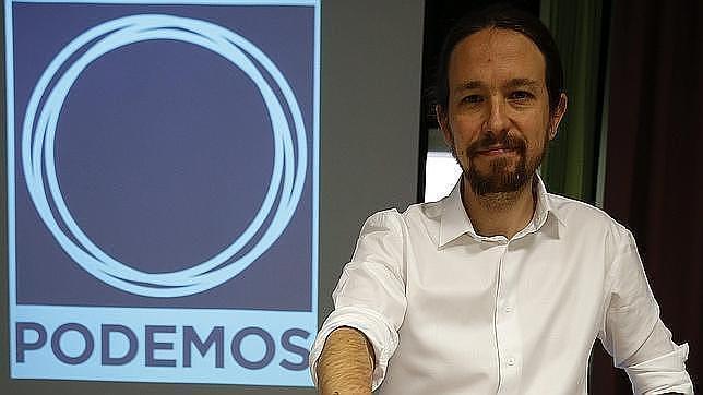 Pablo Iglesias, secretario general de Podemos, junto al logo de la formación