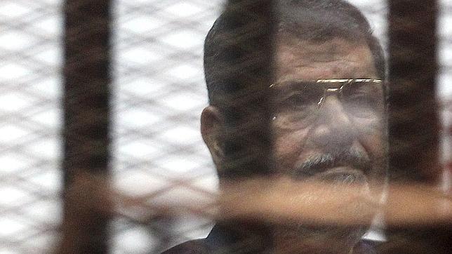 Mohamed Mursi mira tras los barrotes de una celda en el tribunal que ha dictado su sentencia de muerte