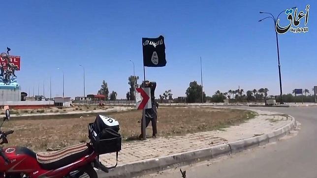 Un combatiente del EI coloca una bandera del grupo en Ramadi