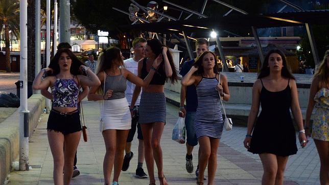 Un grupo de chicas camina por Punta Ballena (Magaluf), detrás sus amigos llevan bolsas con alcohol