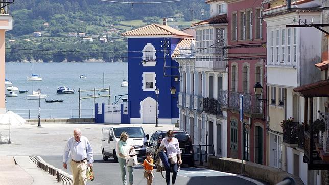 Los turistas se detienen para admirar las coloridas casas que dibujan el coruñés Redes