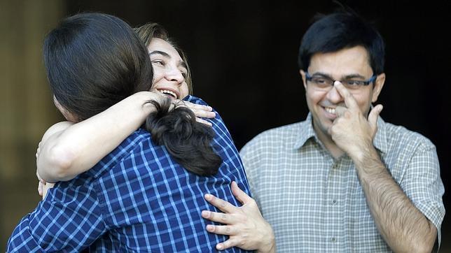 Gerardo Pisarello observa el abrazo entre Colau e Iglesias