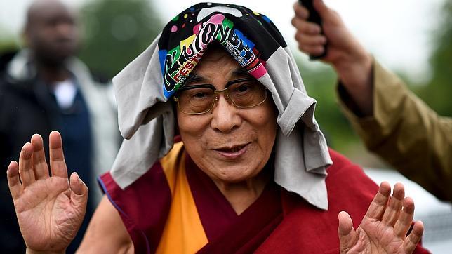 El Dalai Lama se protege de la lluvia con una camiseta de Glastonbury