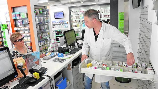 Un farmacéutico atienda a una clienta en la isla griega de Creta