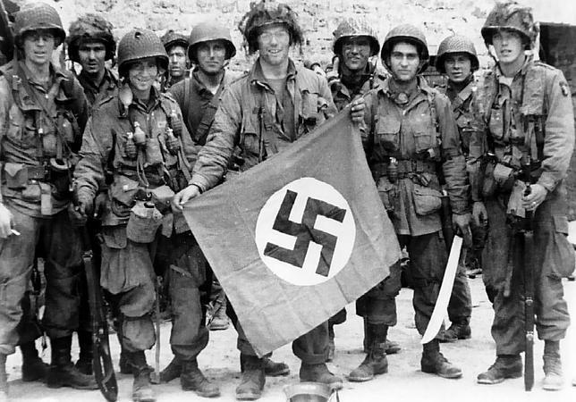Varios miembros de la 101ª División Aerotransportada sujetan una bandera nazi robada