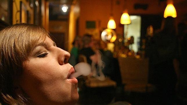 Una mujer fuma en un restaurante