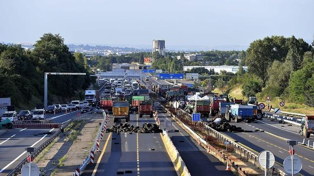 Ganaderos franceses bloquean con camiones y neumáticos una autopista en Limonest, cerca de la ciudad de Lyon (Francia)