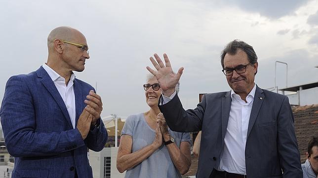 Artur Mas junto con el «número 1» de su lista, Raúl Romeva, y la presidenta de Òmnium, Muriel Casals
