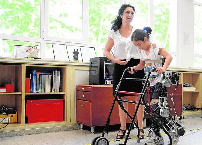 Una niña ayuda a la Elena García, diseñadora del prototipo, en la demostración