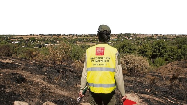 Un agente de las Brigadas de Investigación busca el origen de un incendio reciente