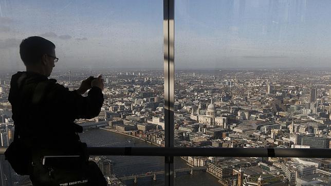 Un hombre hace fotos de Londres desde un edificio junto al río Támesis